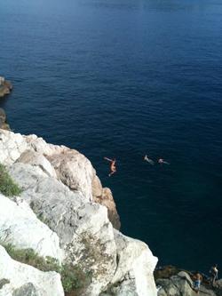 Person hoppar från brant klippa ned i havet
