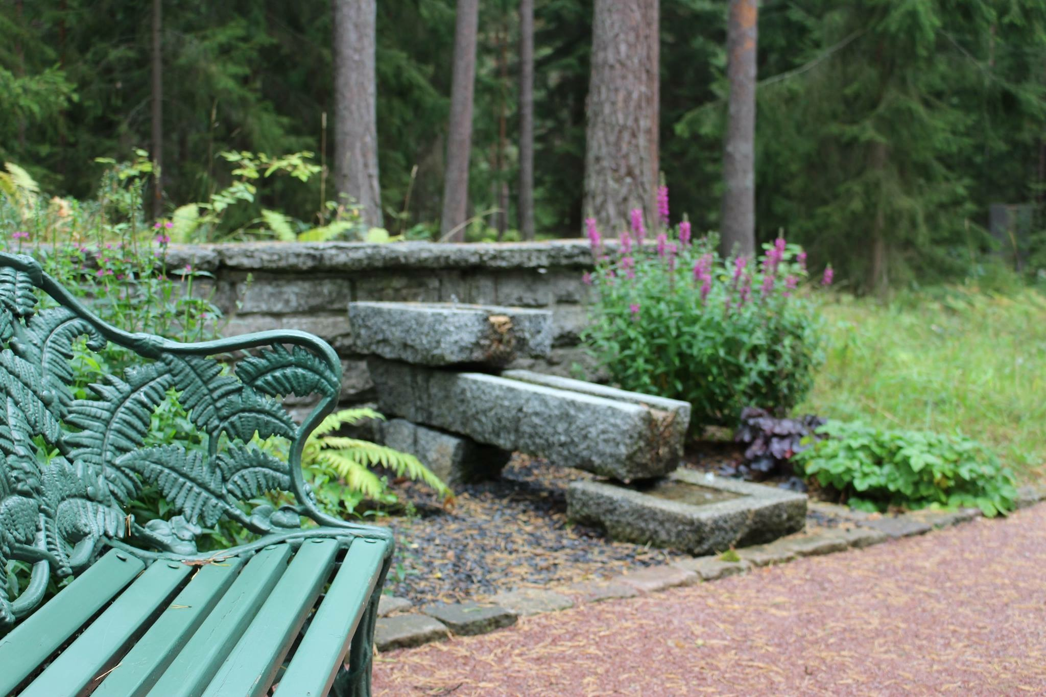 Grön parkbänk stenfontän och rosa blommor