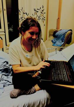 Madeleine på sängkanten med dator